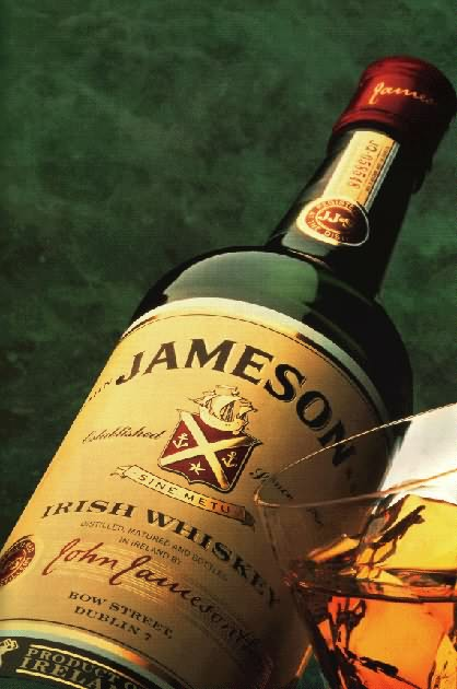 Bottle og Jameson (an Irish whiskey blend) next to a glass of it on the rocks.